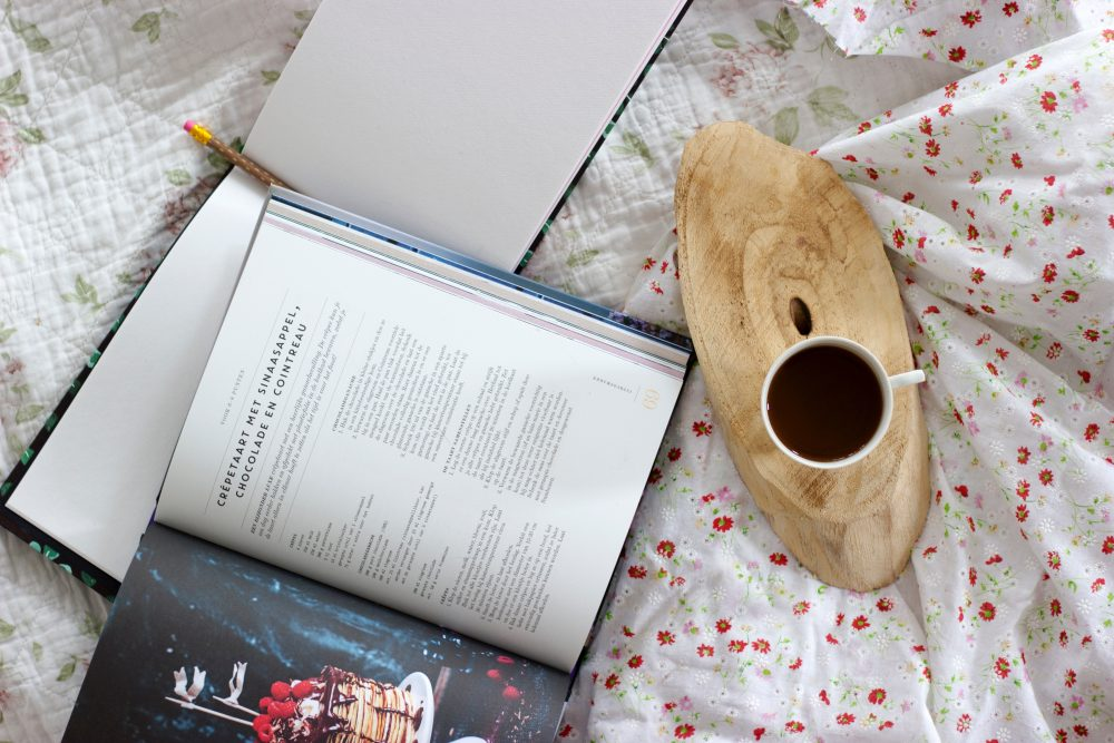 a cook book pictured next to a cup of coffee on pretty bedlinen