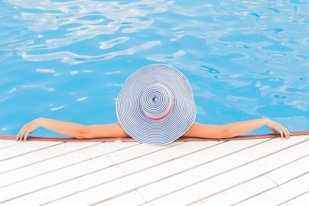 summer style guide, woman in the pool wearing a hat