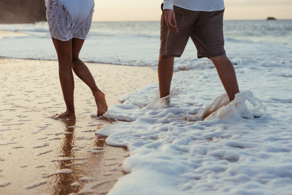 summer style guide, a couple takes a romantic walk on the beach