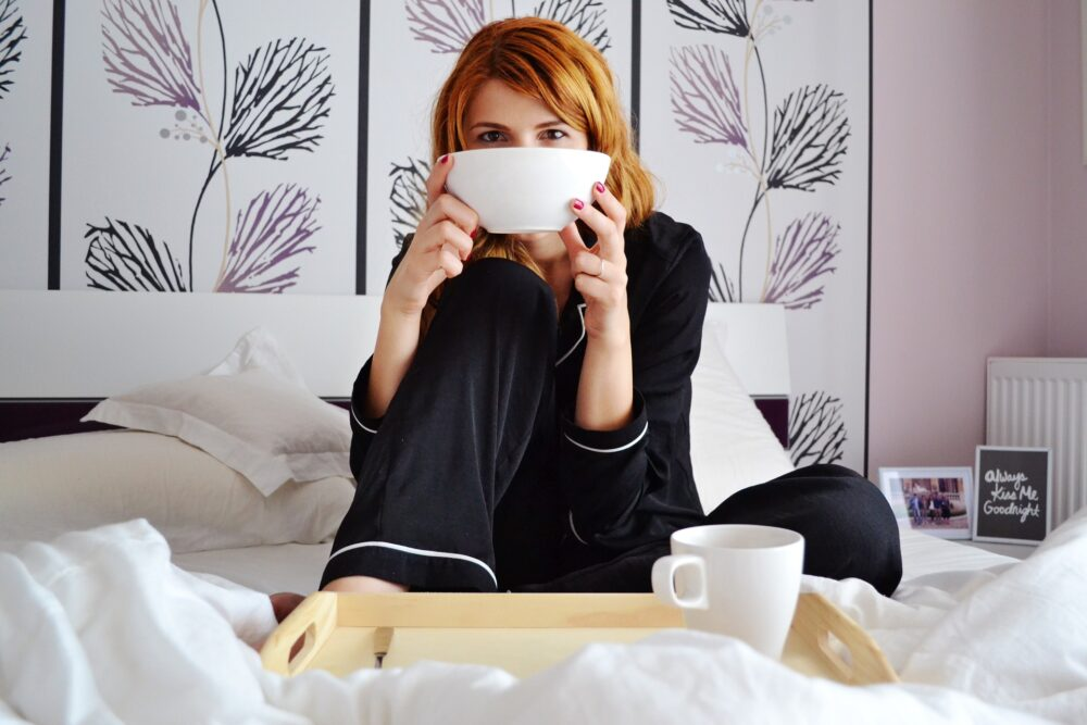 woman drinking tea or coffee in bed