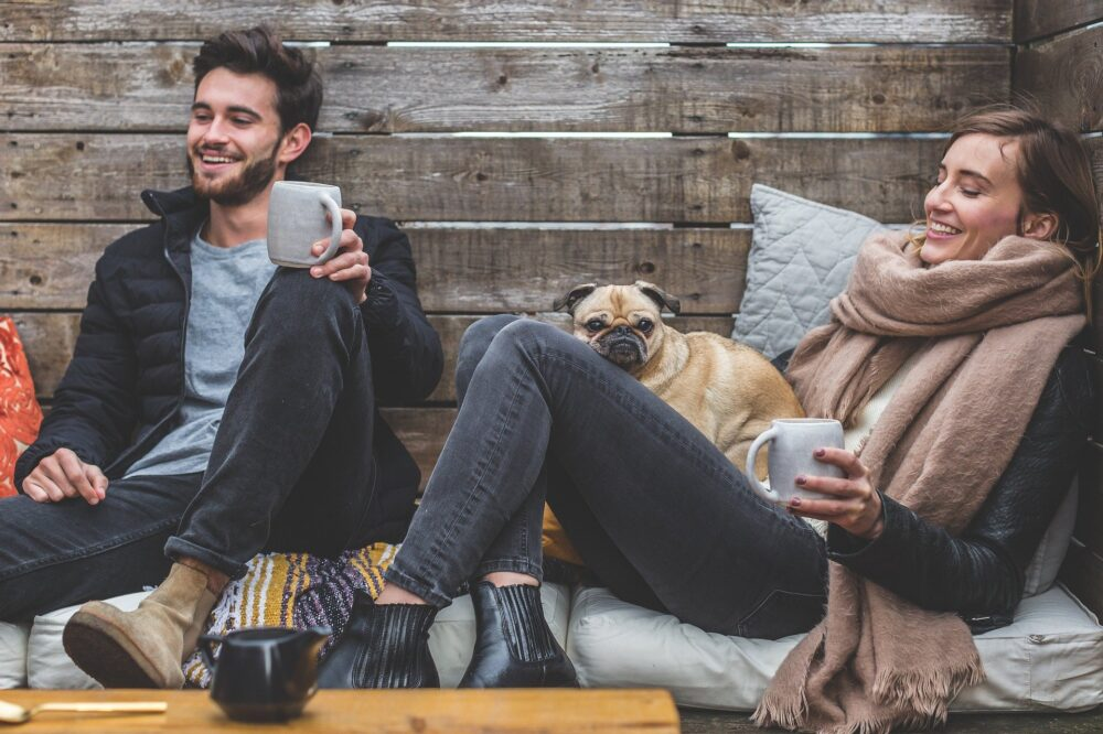 couple enjoying hot drinks indoors with a pet dog