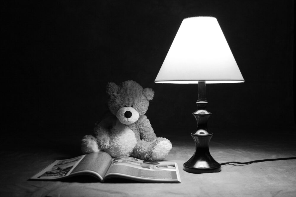 teddy bear under a bedside lamp.