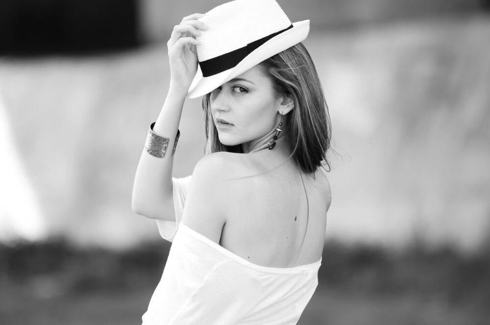 woman wearing hat & earrings